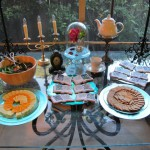 Patio table display for Beauty & the Beast, including my brass candlestick, a small clock, teacup and teapot as you-know-who