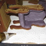 "Purple fondant cushions added to ""carved"" piped gingerbread furniture"