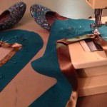 Sewing bronze ribbon trim on the shoes