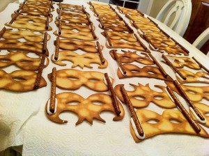 Pretzel rods added with royal icing to the decorated mask cookies