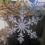 Giant plastic snowflake hanging from the patio chandelier