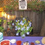 Hanging skull sign over freshly pruned garden bouquet on the patio pizza table