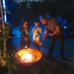 Charles helps Ellie and Benjamin roast their marshmallows for Dia de los S'Muertos