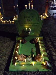 Gravestone with candles alight, some decorations, still needs FLOWERS...