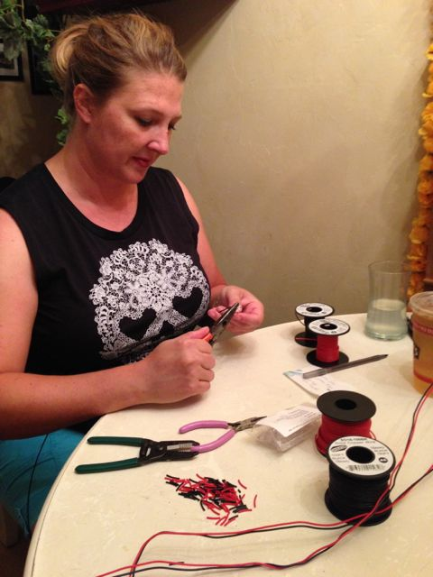 Britta looping the LED leads to the correct colors of wire pigtails before soldering