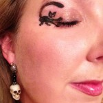 Cat makeup with eye closed with elegant skull earrings