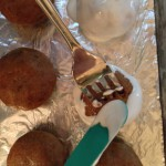 Carefully setting the covered cake ball on the tray and removing the fork