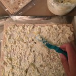Spreading the artichoke dip onto lavash bread for Reboot Rollups