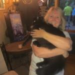 Sheila the cat whisperer snuggles Onyx