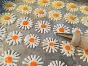 Decorating the daisy centers with food coloring, piping gel & colored sugar