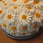 Closeup of layering the daisies onto the fresh meringue frosting