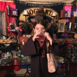 Ellie chugs a Butterbeer Light, aiming the Sorting Hat over her head!